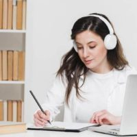Woman with headphones taking notes